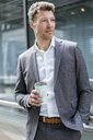 Businessman with takeaway coffee outside in the city - DIGF06855