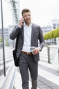 Businessman on cell phone on the move in the city - DIGF06858