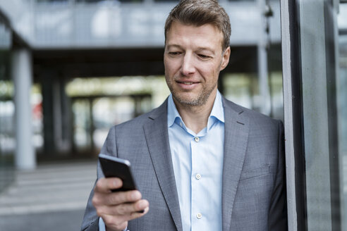 Portrait of businessman looking at cell phone outdoors - DIGF06891