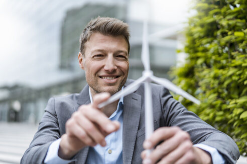 Businessman with wind turbine model outdoors - DIGF06894