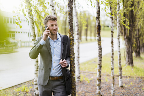 Businessman on cell phone in a park - DIGF06906