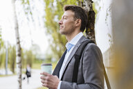 Relaxed businessman with takeaway coffee in a park - DIGF06909