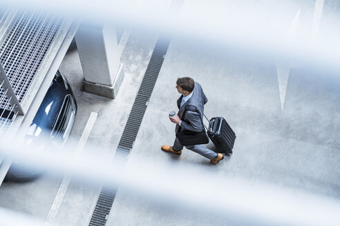 Top view of businessman walking with baggage and takeaway coffee at a car park - DIGF06912