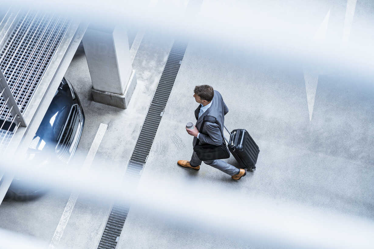 Top view of businessman walking with baggage and takeaway coffee at a car park - DIGF06912 - Daniel Ingold/Westend61