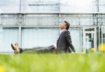 Relaxed businessman having a break sitting in grass - DIGF06921