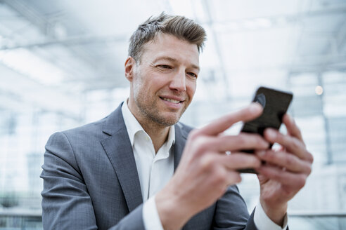 Portrait of smiliing businessman using cell phone - DIGF06927
