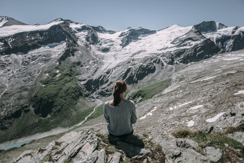 Caucasian woman sitting on rock admiring scenic view of mountain - BLEF02030