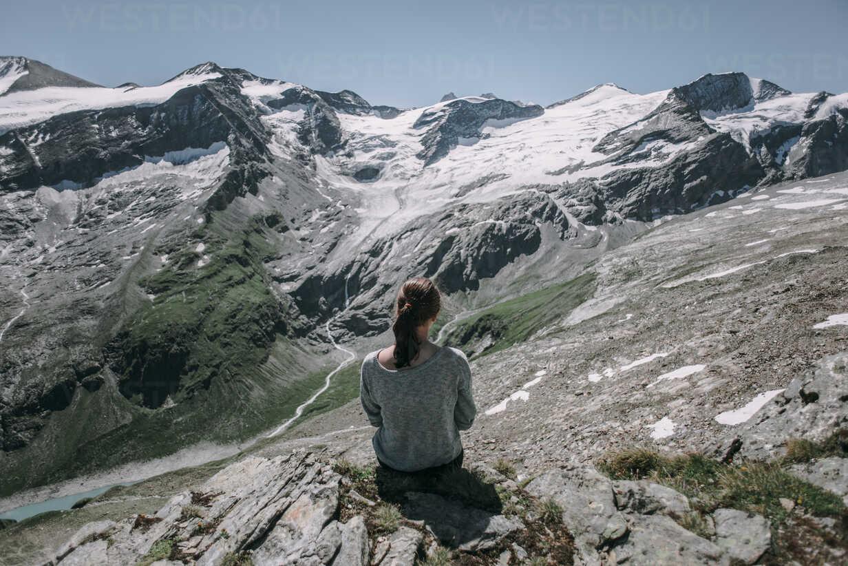 Caucasian woman sitting on rock admiring scenic view of mountain - BLEF02030 - Alexey Karamanov/Westend61