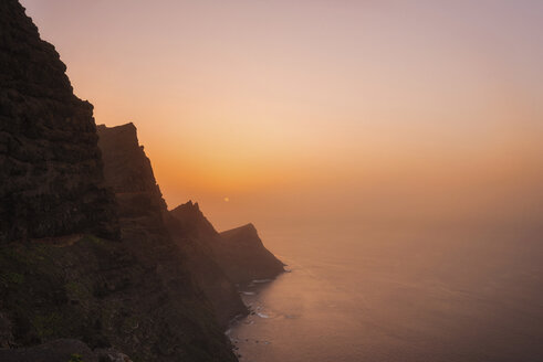 Spain, Gran Canaria, rocky cliff at sunset - DHCF00194