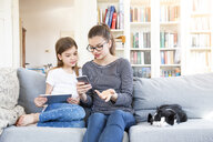 Two sisters sitting on the couch at home using electronic devices - LVF08007