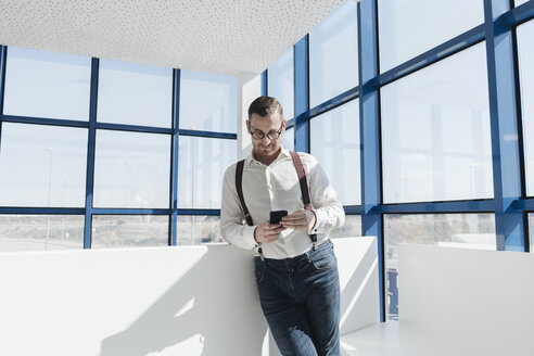 Businessman using cell phone at the window in modern office - AHSF00212