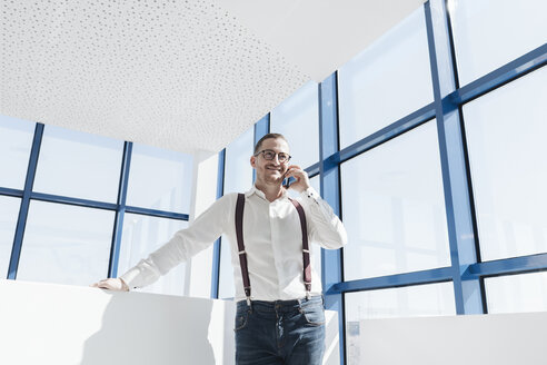 Businessman talking on cell phone at the window in modern office - AHSF00215