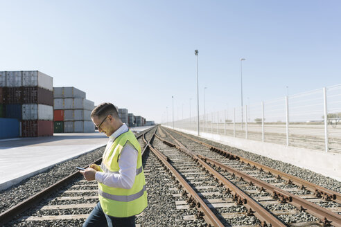 Man on railway tracks in front of cargo containers using cell phone - AHSF00221