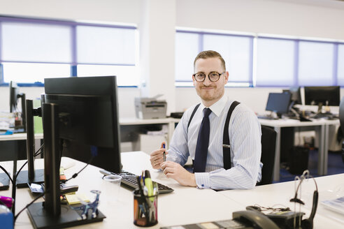 Portrait of confident businessman at desk in office - AHSF00236