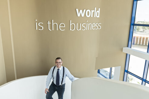 Portrait of confident businessman walking up stairs in modern office - AHSF00242