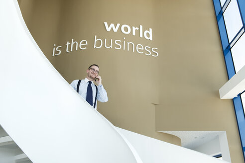 Businessman talking on cell phone on stairs in modern office - AHSF00245