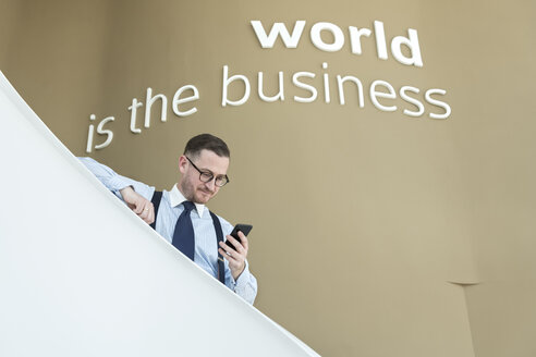 Businessman using cell phone on stairs in modern office - AHSF00248