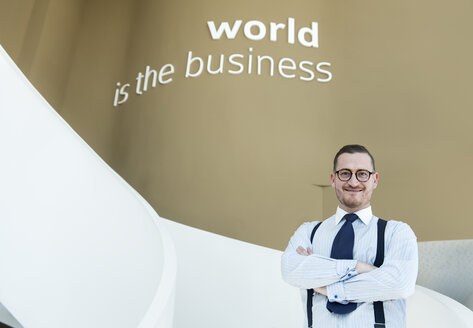 Portrait of confident businessman on stairs in modern office - AHSF00251