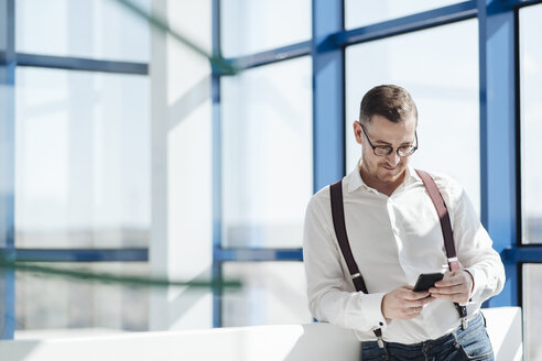 Businessman using cell phone at the window in modern office - AHSF00257