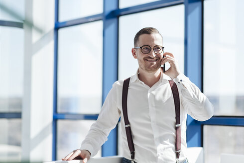 Smiling businessman talking on cell phone at the window in modern office - AHSF00260