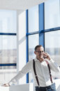 Happy businessman talking on cell phone at the window in modern office - AHSF00263