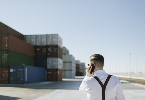 Spain, Aragon, Zaragoza, manager in logistic center near to containers with goods speaking by phone - AHSF00272
