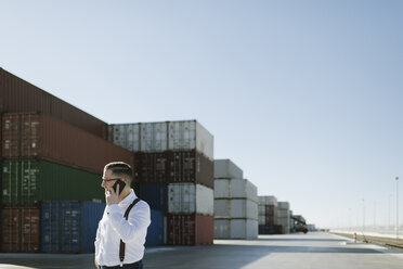 Manager talking on cell phone in front of cargo containers on industrial site - AHSF00275