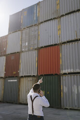 Rear view of manager talking on cell phone in front of cargo containers on industrial site - AHSF00278
