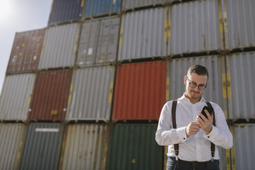 Manager in front of cargo containers on industrial site using cell phone - AHSF00281