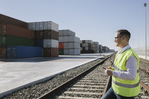Man on railway tracks in front of cargo containers holding cell phone - AHSF00284