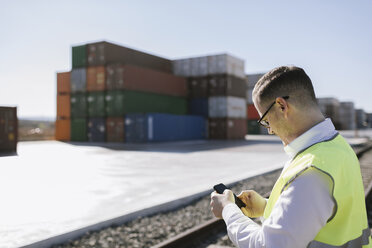 Man on railway tracks in front of cargo containers using cell phone - AHSF00287