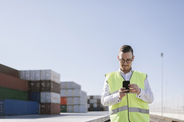 Man on railway tracks in front of cargo containers using cell phone - AHSF00290