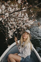 Japan, Tokio, Chidorigafuchi Park, woman in rowing boat admiring cherry tree blossom - LHPF00707