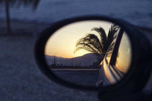 Greece, reflection of palm in wing mirror of a car at sunset - MAMF00662
