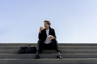 Businessman sitting on stairs having lunch break - AFVF02837