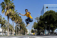 Spain, Barcelona, man in the city jumping on the street - AFVF02885