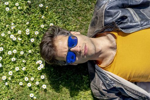 Man lying on flower meadow wearing sunglasses - AFVF02888