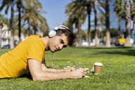 Spain, Barcelona, man lying on lawn in the city with headphones and notebook - AFVF02891