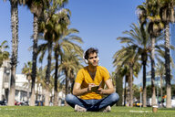 Spain, Barcelona, man sitting on lawn in the city with headphones and notebook - AFVF02894