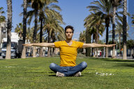 Spain, Barcelona, man practicing yoga on lawn in the city - AFVF02897