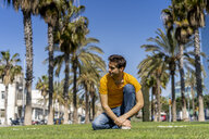 Spain, Barcelona, man on lawn in the city looking around - AFVF02900