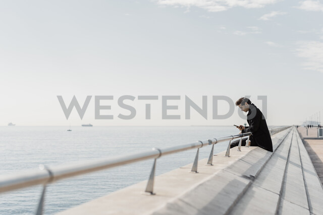 Businessman sitting on quay wall checking cell phone - AFVF02903 - VITTA GALLERY/Westend61