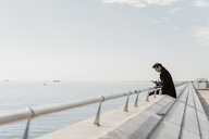 Businessman sitting on quay wall checking cell phone - AFVF02903