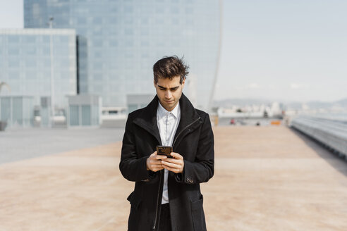 Businessman using cell phone in the city - AFVF02906