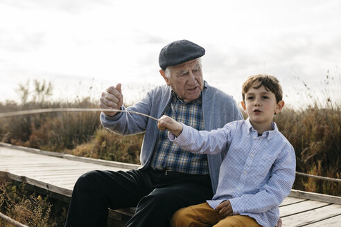 Grandfather and grandson sitting with on boardwalk relaxing - JRFF03185