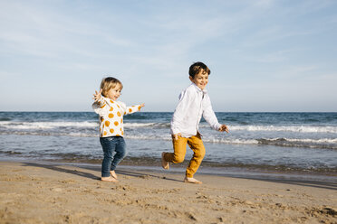 Boy and his little sister playing on the beach - JRFF03209