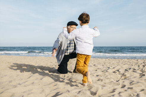 Grandfather playing with his grandson on the beach - JRFF03212
