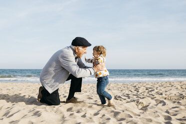 Grandfather playing with his granddaughter on the beach - JRFF03218