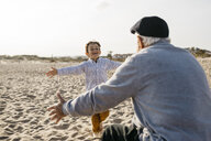 Portrait of happy little boy running into his grandfather's arms on the beach - JRFF03221