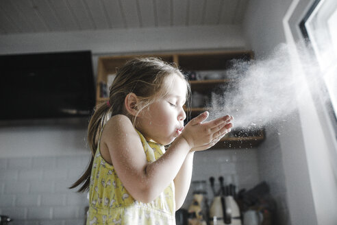 Little girl blowing flour in the air in the kitchen - KMKF00905